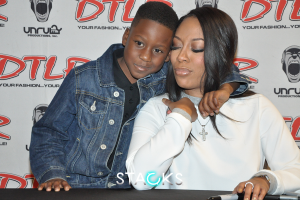 R&B singer K. Michelle embraces one of her younger fans.